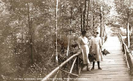 black and white of women walking over a bridge